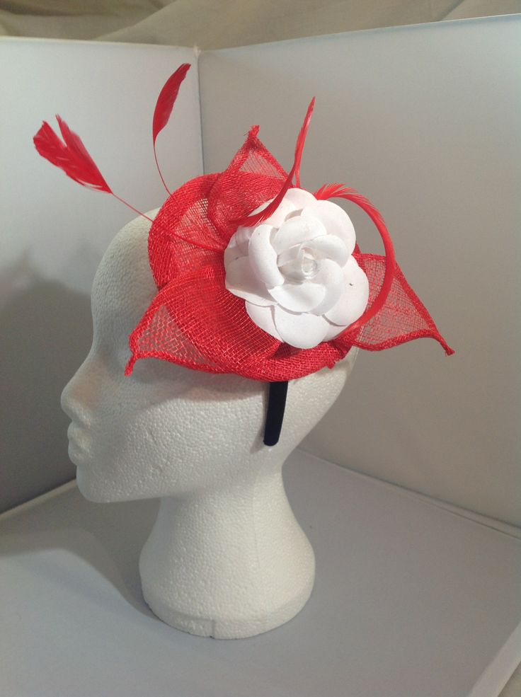 The Gloria is a small fascinator on a black head band the base is ruby sinamay with a centre piece of a diamond white flower surrounded by ruby red sinamay leaves and matching feathers to finish. $70 AUD.