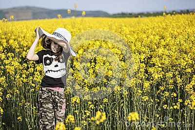 Young girl with sunhat in canola , rapeseed crop field