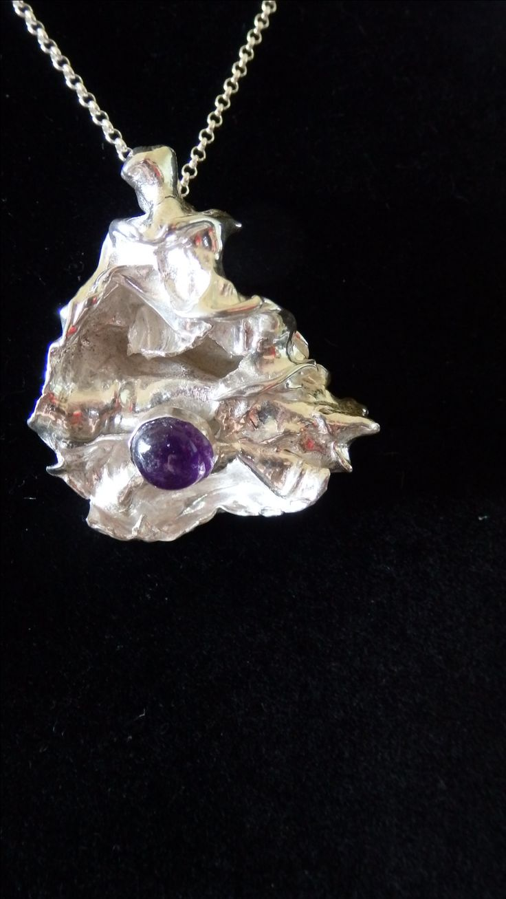 Free form organic shape, sterling silver pendant with Amethyst cabochon; sterling silver chain.