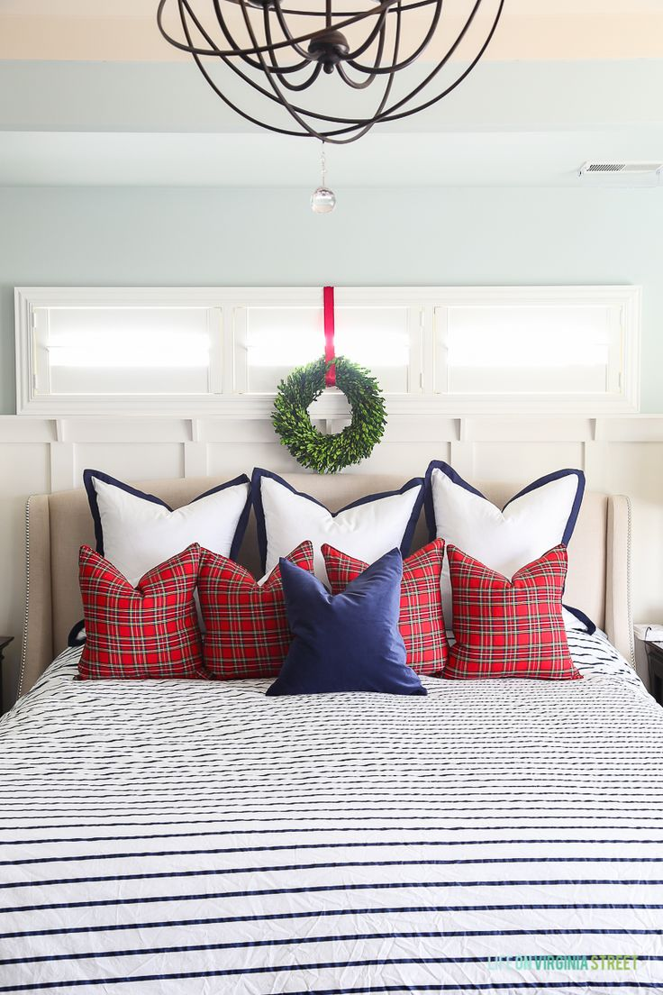 Christmas master bedroom with red plaid pillows, and navy blue and white stripes. Love the boxwood wreath over the bed!