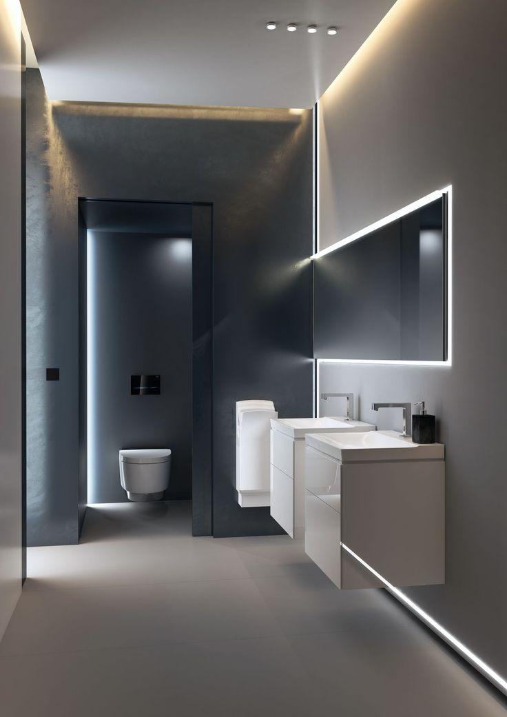 Deze minimalistische badkamer speelt met strakke lijnen en sobere grijstinten. De indirecte lichtpartijen zorgen voor een extra ruimtegevoel. ••• Cette salle de bains minimaliste joue avec des lignes épurées et de sobres nuances de gris. Les zones indirectes de lumière donnent un sentiment d'espace supplémentaire.