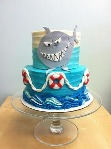 LOVE!! This cake, minus the cartoon shark. With realistic fondant sharks, fins, boat topper, life preservers and name plate.