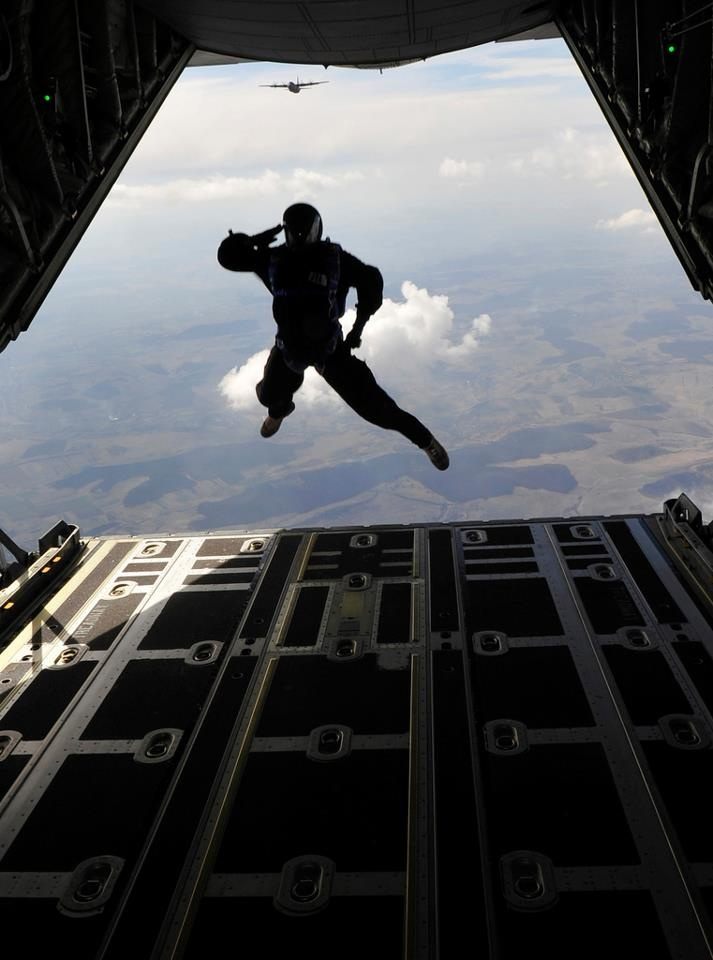 """US Air Force Pararescueman (Pararescue Jumper) a.k.a. """"PJ"""" jumping out of the back of an aircraft with a departing salute. These are the guys who rescue downed pilots, NASA astronauts, other fallen soldiers in the battlefield AND rescue the US Navy's SEALS when needed!"""