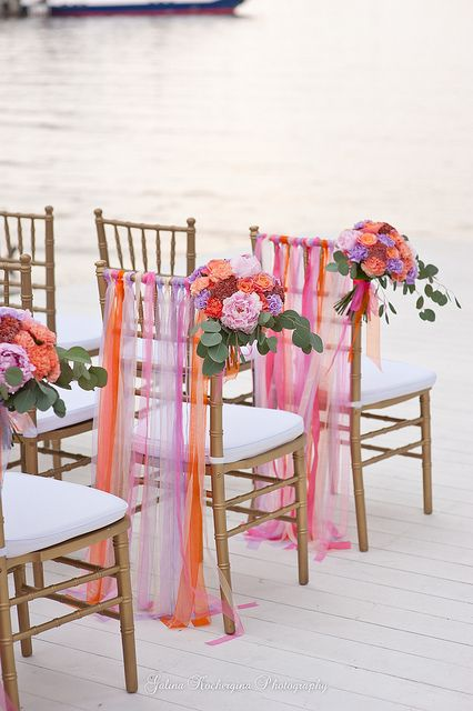 colourful wedding ceremony chairs - nice could do this with ribbon or cheap organza material cut into strips :-)