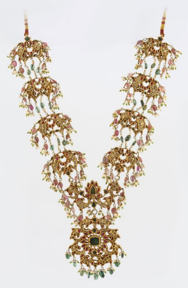 A GEMSET 'FISH' NECKLACE. Intricately designed as a series of openwork links in the form of a pair of stylized fish, and kundan-set with table-cut 'polki' diamonds, weighing approximately 6.50 carats, along with fringes of various gems like emerald beads, spinel beads, and seed pearls, with a total gemstone weight of approximately 120.00 carats, suspending an openwork pendant of similar design, mounted in gold, and joined by an adjustable silk cord.
