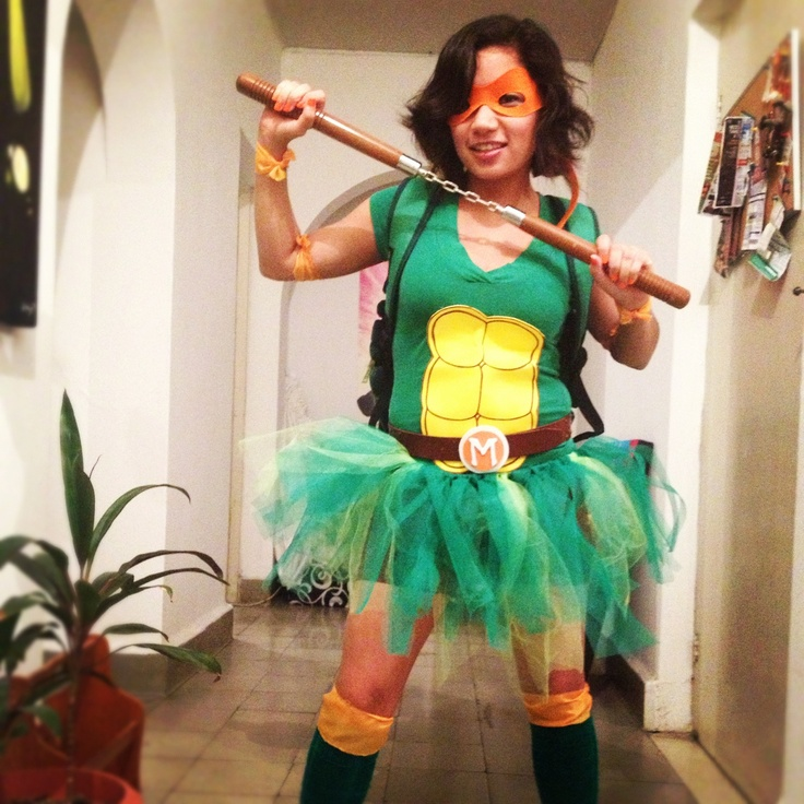 "Homemade TMNT costume. --would use t-shirt-hot glue and/or iron-on adhesicve, felt for front, fluffier DIY green tutu with elastic and knotted fabric of multiple colors (dark green, light green & glittery green) &  black leggings with knee pads and green athletic socks . 2"" ribbon & felt for masks and belts (and other accents)... <$35 per costume"