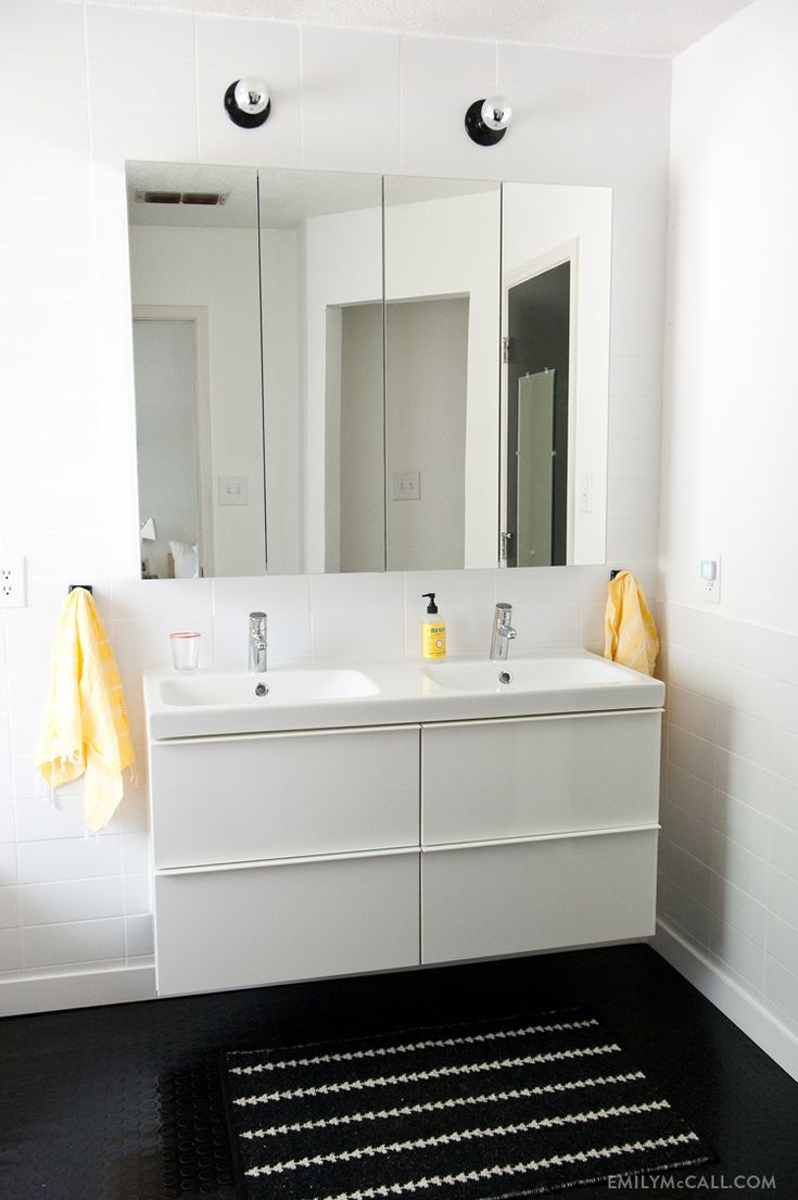 Master bathroom with IKEA GODMORGON mirrored medicine cabinets and high gloss white sink cabinet, ODENSVIK sink, Nate Berkus for Target rug, and yellow Turkish bath towels