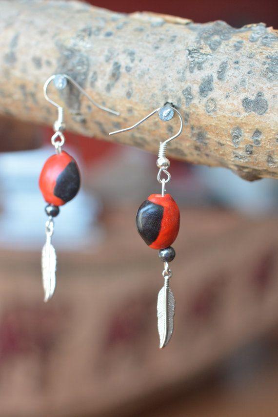 Boucles doreille en métal et graines de huayruro, symbole plume, crochet en métal ou argent (oreilles sensibles).  Les graines rouges de huayruro