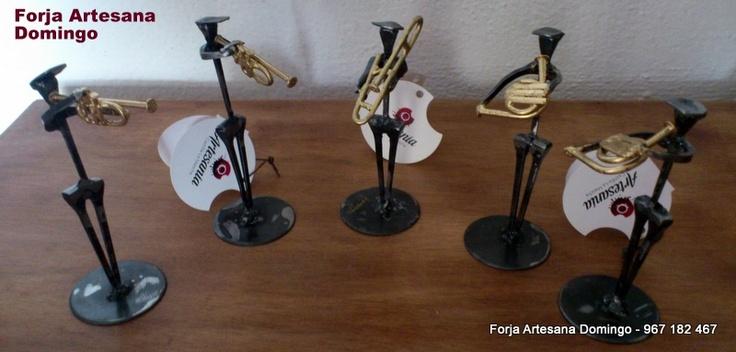 Figuras de forja de músicos realizados con clavos de herrar de forma artesana tocando la trompa, trompetas y trombón.
