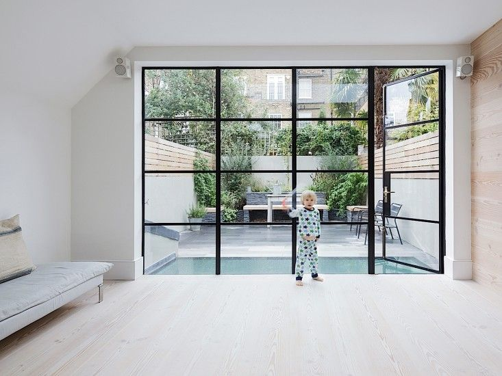 House in Fulham by Studio Ore, Photography by Rory Gardiner | Remodelista. Custom steel-and-glass doors optimize the amount of natural daylight that comes into the space.