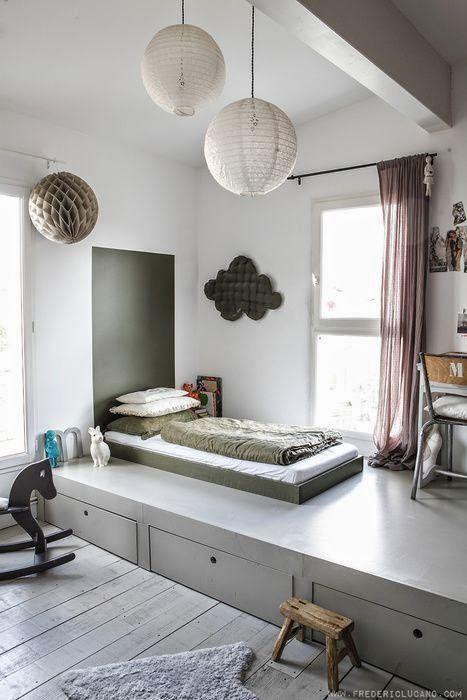 Un coin chambre structuré par une estrade basse grise avec des tiroirs