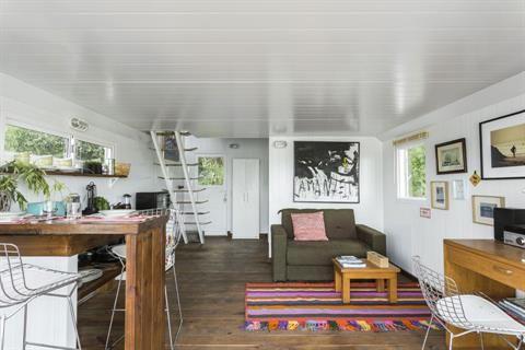 3 vecinos nos muestran sus casas con estilo vanguardista  En el living, sillón marrón, almohadón tramado ($499, Falabella) y mesa ratona sobre alfombra rayada con flecos ($3.995, Elementos Argentinos). A la derecha, un pequeño escritorio de MDF con silla 'Bertoia'. Para la original escalera, se usaron tablas de longboard como escalones Foto:Daniel Karp