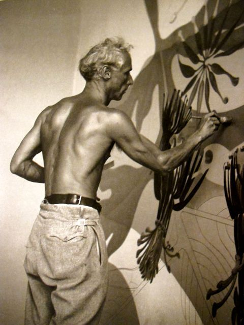 Max Ernst working, sans shirt, on his murals  for the Corso Bar.  Zurich 1934