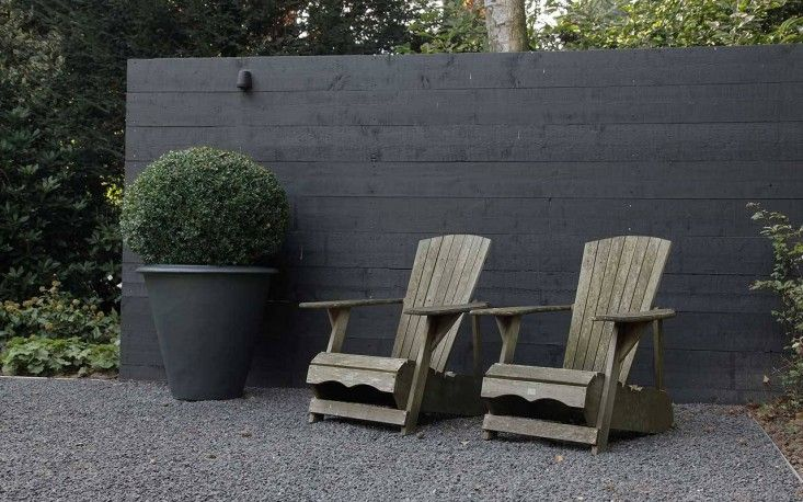 Black fence, black pot and dark grey graded pebbles. Pinned to Garden Design - Walls, Fences & Screens by Darin Bradbury.