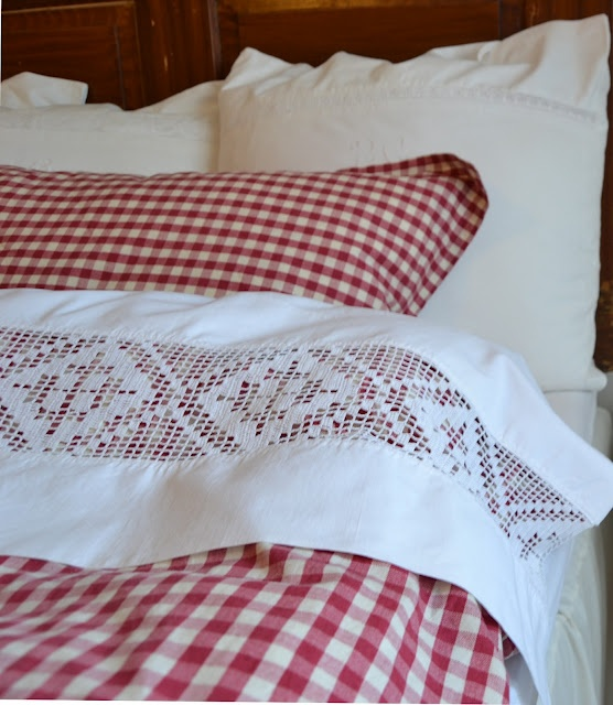 Perfect Bed!  I love red ginghams (or red plaids) and crisp, white linens with lace trim!  The Emmie Spets sheets from Ikea are very similar in style to the gorgeous top sheet here.