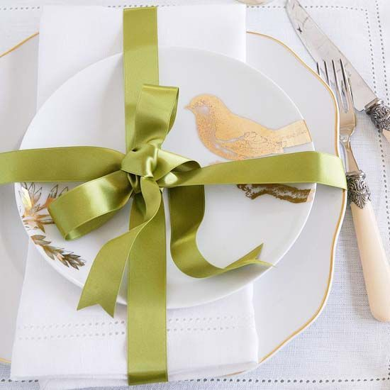 Gift-Wrap your place settings.  Layer napkin between holiday dishes & tie a pretty bow.