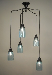 Pictured is our one-of-a-kind Spyder Chandelier featuring 5 ball jars hung at various lengths from a vintage brass base.