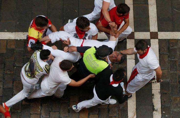 Varias personas socorren a un herido durante el tercer encierro de San Fermín 2016.