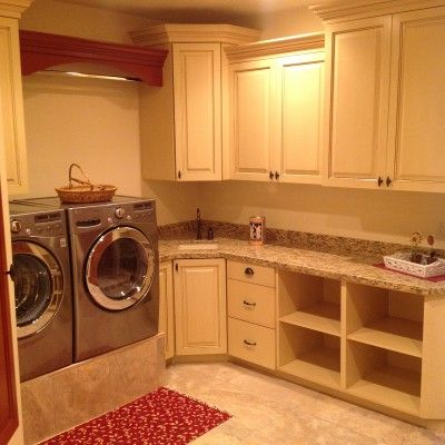 Raised washer and dryer in laundry room, counter space, white cabinets, storage space, CF Olsen Designs