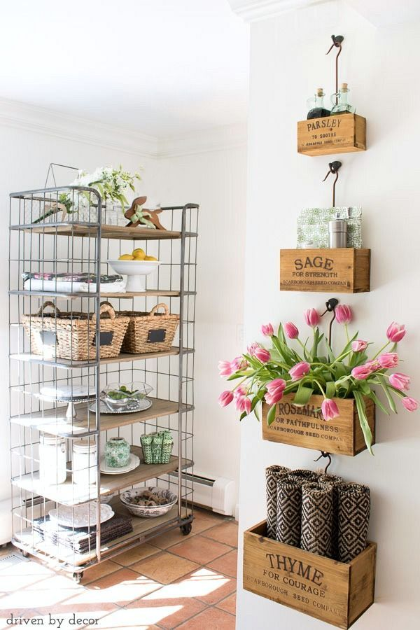 Kitchen with farmhouse style - wall-mounted nesting herb crates filled with tabletop necessities and farmhouse baker's rack