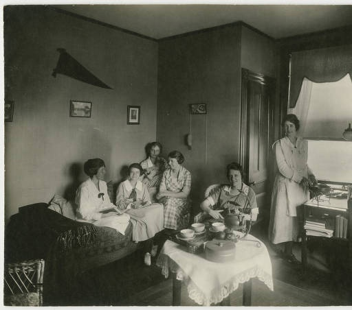 Six students gathered in a dormitory room, with Madeline Barlow, Class of 1921, pictured on the far left :: Archives & Special Collections Digital Images :: ca. 1920