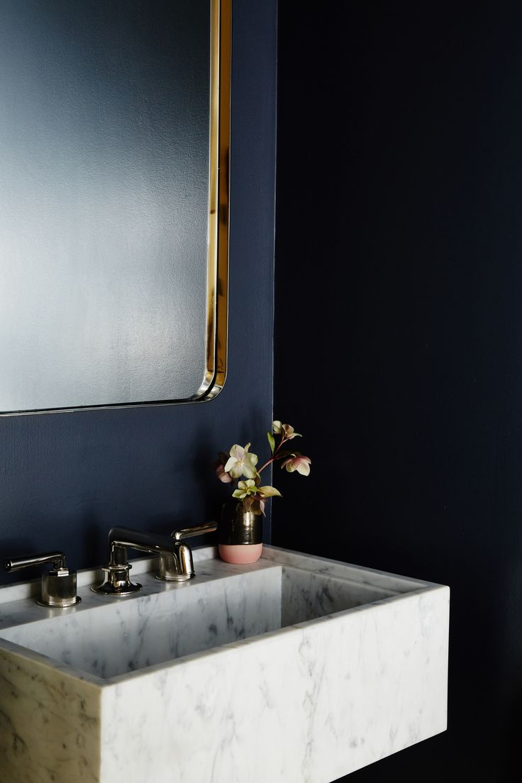 Chic dark blue powder room features a marble wall mounted sink finished with a polished brass faucet kit | Studio Muir