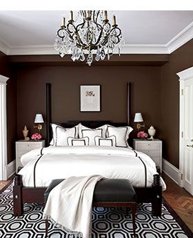 Bedroom - brown walls - accent pattern - In this light-filled room, dark brown walls create a calm mood. The mix of brown and white patterns provide interest. The sparkling chandelier adds sparkle; crisp white elements add punch. The wall color is Benjamin Moore's Sierra Spruce (2108-20). (From Traditional Home. Photo: Werner Staube.)