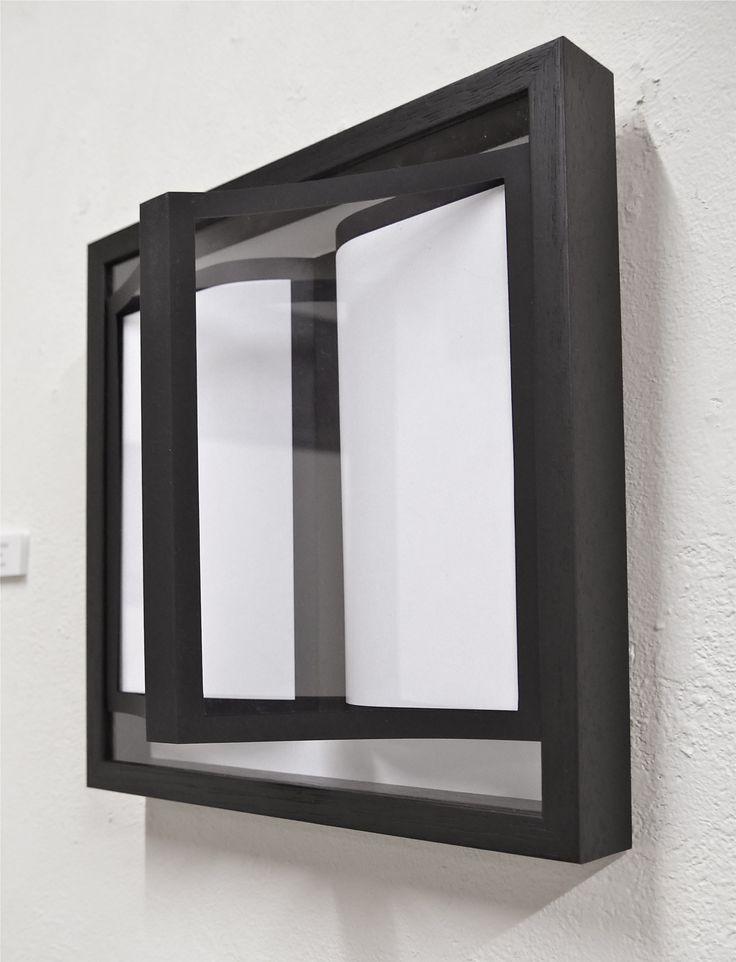 「対峙する本」 額の中には見開きの本。額のガラス面が鏡であるかのように、ガラス面上には見開きの本の「鏡像」の輪郭のみが見える。