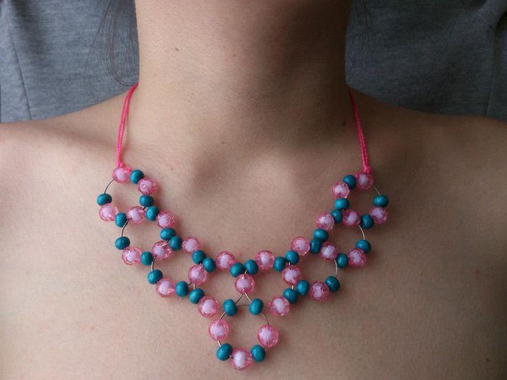 Collar de alambre y perlas de madera y plástico con lazo de hilo.