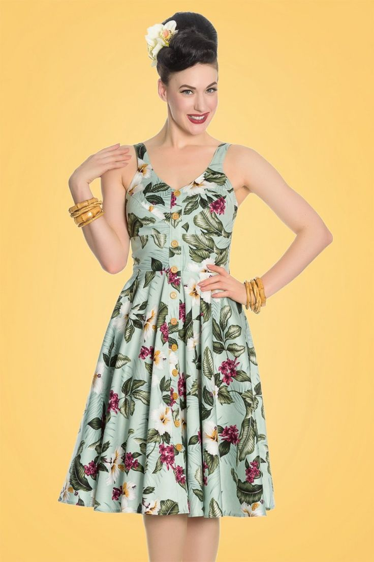 """Deze 50s Tahiti Floral Swing Dresswordt het pronkstuk van je jurkencollectie! Trek je pumps maar aan en zet je favoriete plaat maar op want het is tijd om te dansen van vreugde!De aansluitende top en swing rok zorgen ervoor dat jij een super vrouwelijk silhouet hebt, oh la la. Het lijkt alsof het een doorknoop jurk is maar niets is minder waar; het is een reeks houten """"faux'' knoopjes. De luchtige en soepel vallende, mintgroene katoenmix heeft een lichte stret..."""