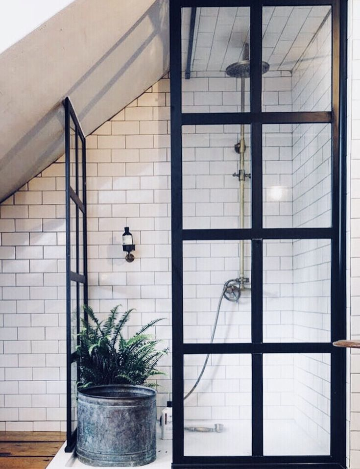 Modern farmhouse style attic bathroom with a walk-in shower. Corner shower features white subway tile and a black frame Gridscape Series True Divided Light Factory Window Shower Screens. #modernfarmhouse #farmhousebath #bathroomdesignideas #showerdesignideas #cornershower #bathroomdesign #atticbath  Image Source: Design Sponge | http://www.designsponge.com/2016/10/built-in-the-1830s-a-designers-cozy-curated-cottage.html | Built in the 1830s, a Designer's Cozy & Curated Cottage by Garrett…