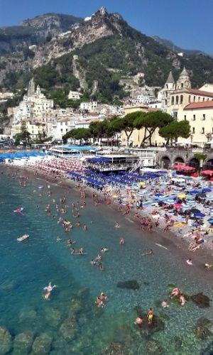 Turistas nadam no mar da vila de Amalfi, um dos mais concorridos destinos de toda a Costa Amalfitana, no sul da Itália