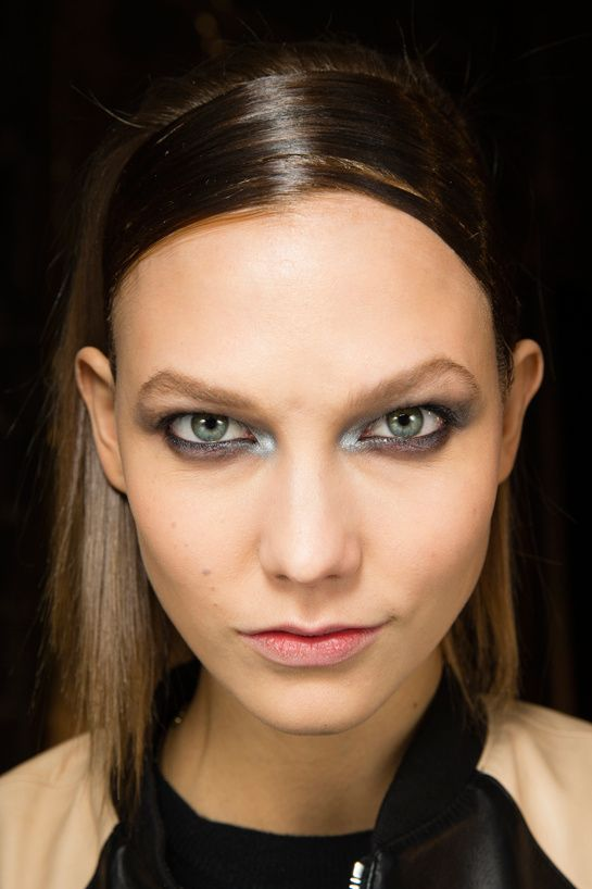 The eyes was lined in black and silver shadow was used for a smokey effect, pairing the look with dewy skin at Donna Karan FW 2014