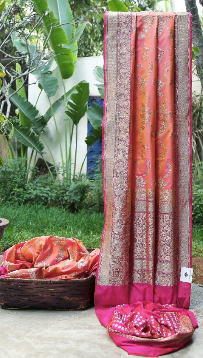 This iridescent tulip pink and orange Benares silk has gold and silver zari flowers woven all over the sari. The border and pallu are in magenta that is intricately woven with gold zari giving it a...