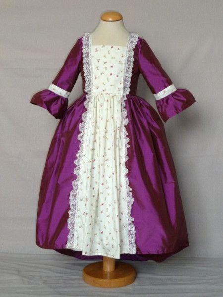 robe de marquise en taffetas violine, coton fleuri et dentelle décrue courant sur l'encolure et allant jusqu'en bas de la robe. boutonnage dos. petite traîne. présentée avec jupon, livrable séparément.
