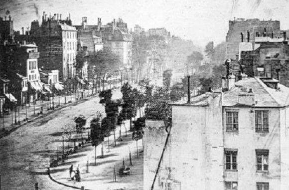 これは写真の歴史の一つとして過去にもカラパイアで紹介したものだ。 1838年、パリに住むある住人がブールバール寺院で靴を磨いてもらうために立ち止まったことから、偶然にも歴史に残ることになった。まさにその瞬間、ルイ・ダゲールが付近にあった建物の屋上から自身が発明したダゲレオタイプで、通りの写真を撮影していたのだ。露出が終わるまでに7分かかったため、道路に往来は何も写っていない。だが、このパリの男性は、たまたまそこで7分間動かずに時間を費やすことになった。その結果、彼は歴史上初めて記念すべき写真の被写体となった。だが、彼についてそれ以上のことは何も分からない。   彼の生涯、容姿、仕事、収入、理想、家族、出自など、一切が闇に包まれている。彼がパリ人で、本当に靴を磨いてもらっていたのかさえ定かではない。水のポンプの前に立っているという説もあるほどだ。また、写真に写っているのは彼だけではないとする説もある。靴磨きの少年は動きが激しく写っていないが、窓から覗くぼやけた人影らしきものもまた、無名の栄誉に浴していた人物だった可能性がある。