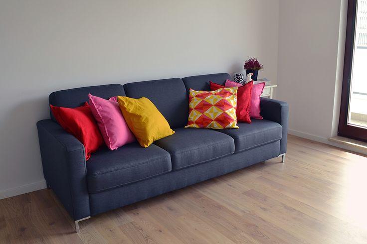 Minimalistyczna, szara kanapa. Dzięki kolorowym poduszkom nabrała charakteru! :)