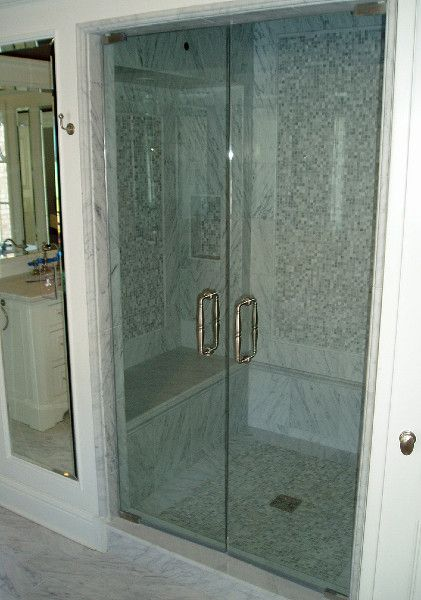 Frameless shower swing doors with Victorian style back-to-back handle installed by Binswanger Glass.
