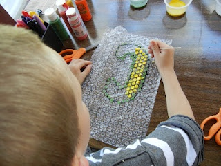 Bubble Wrap Printing:  create a sack lunch for a picnic.   Pre-draw a big bubble letter (the first letter of kids name) on the smooth side of the wrap with a Sharpie.  Then let kid use a Q-tip to dab paint onto the bubble wrap, filling in the inside of the letter.  Once all of the paint is dabbed on (and before it dries) transfer the design to the paper sack by laying the bubble wrap, paint side down, on the sack and press gently.