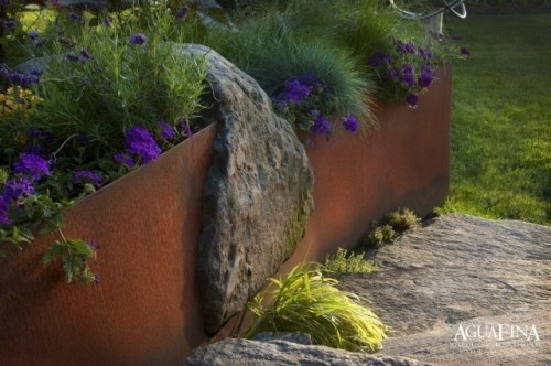 Striking Stone Designs    The steel sides of this raised bed surround a large boulder for a waterfall effect. The rock seems to cascade over the sides of the planter.