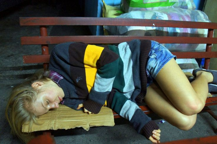 A girl is sleeping at the bus stop in Laoag