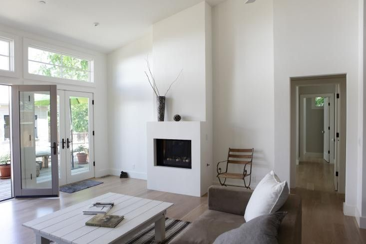Renovated cottage with modern white fireplace, Remodelista-the fireplace, just add a wood storage section on one side and this is what I want