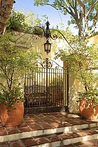 Use of large potted plants as visual  support for iron gateway. The lantern truly makes it!
