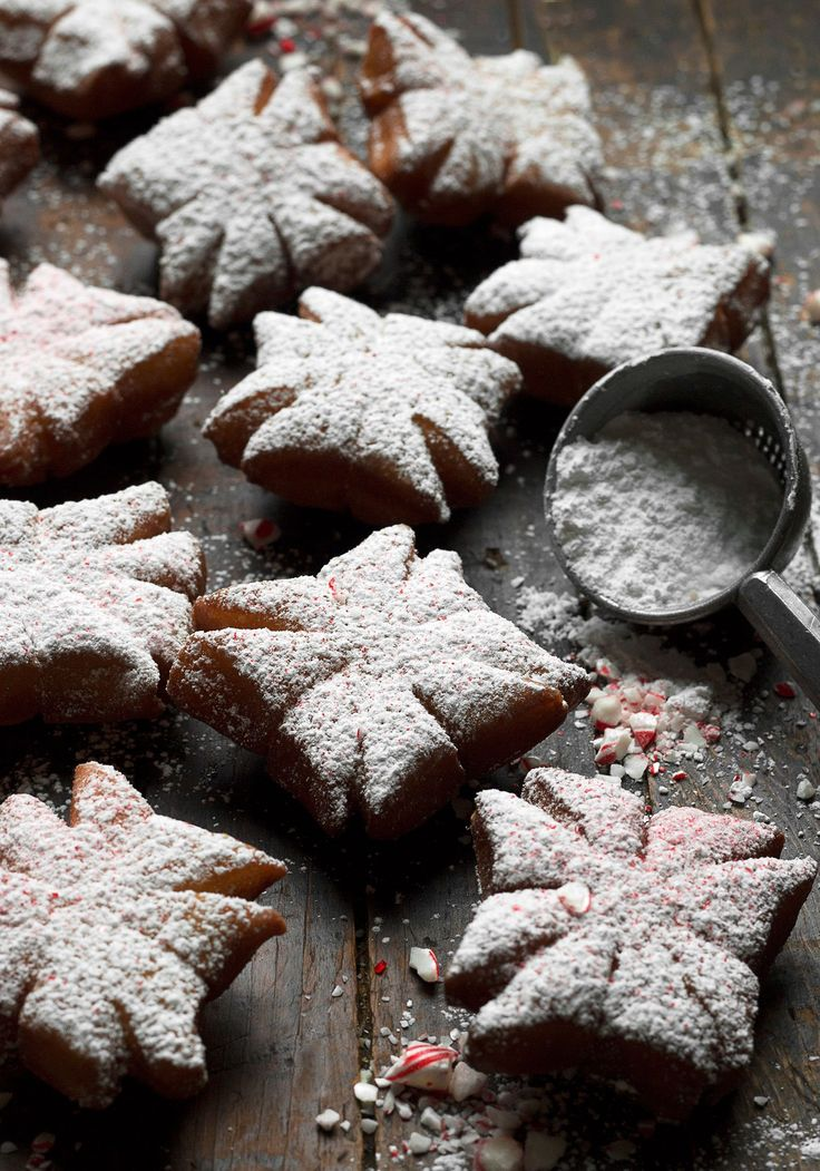 Peppermint Snowflake Beignets - The simple snowflake pattern involves just a sharp knife to cut slits into a square of dough. The dough is quickly fried, then dusted with icing sugar and finely crushed candy canes and enjoyed warm. #FriedDessert #BeignetRecipe #Fritters #Peppermint #Recipe #HolidayDesserts #ChristmasDesserts