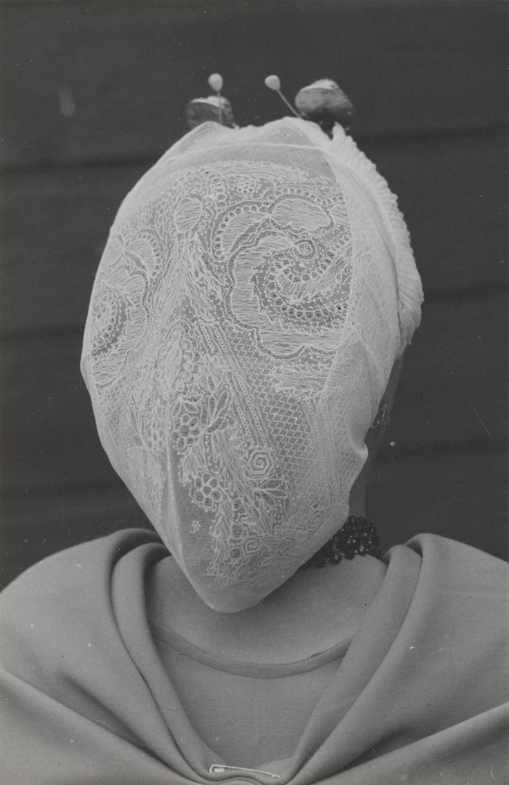 Vrouw in Scheveningse streekdracht, zondagse dracht anno 1953. Ze is 'in het gekleurd' (niet in de rouw). Ze draagt een 'blonde' (kanten) muts, met 'ronde klappen' (zijkanten). Onder de muts een zilveren oorijzer met ovale gouden 'boeken' aan de uiteinden. Achter de boeken zijn twee gouden steekspelden met parel in de muts gestoken. De schouderdoek is aan de achterzijde voorzien van enkele plooien, welke met een veiligheidspeld bijeen worden gehouden. #ZuidHolland #Scheveningen