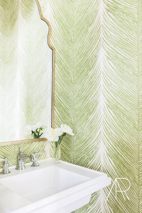 Jason Arnold Interiors - Stunning contemporary green and gold powder room features walls lined with Mey Fern wallpaper by Nina Campbell accenting a gold arched mirror hung above a wall mounted white porcelain sink completed with a polished nickel faucet.