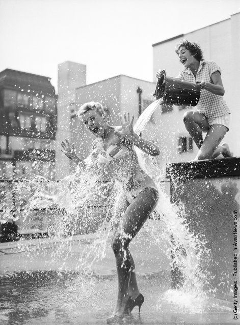 Two actresses cool off this day in 1959 on the roof of the Piccadilly Theatre in London.