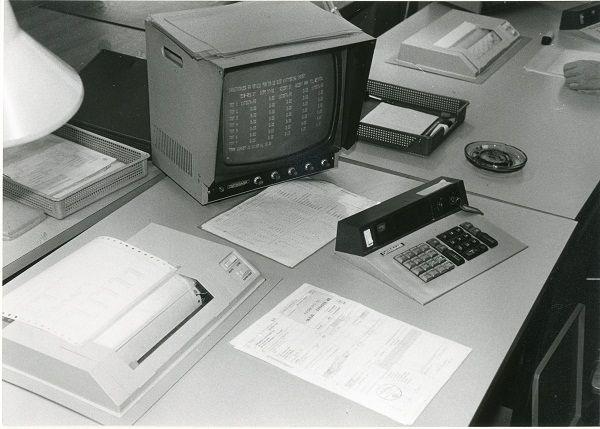 """Billedet viser en typisk arbejdssituation i Toldvæsnet i 1985. Til højre ses et askebæger – det var mere reglen end undtagelsen at der blev røget på kontoret under arbejdet. At tage hensyn til ikke rygerne var ukendt og slet ikke noget der var oppe i den offentlige debat endnu. Skærmen var naturligvis en sort/hvid skærm og de programmer, der blev brugt, var fortsat ikke løsninger, hvor der var tænkt på brugervenlighed. """"Edb kom før brugeren – og ikke omvendt""""."""