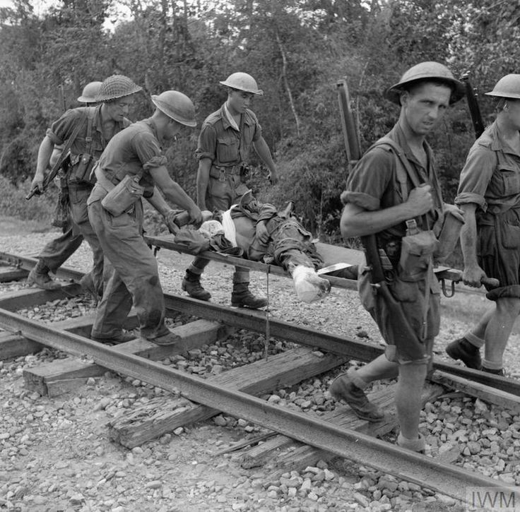 A wounded prisoner is carried on a stretcher along a railway track by troops of 36th Infantry Division during the advance on Mawlu, November 1944.