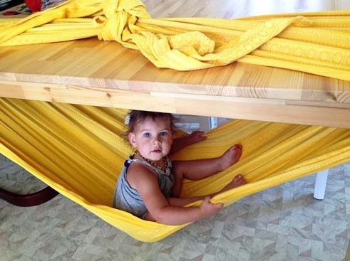 Need a place to put your kid? Make a hammock with a blanket tied around a table.
